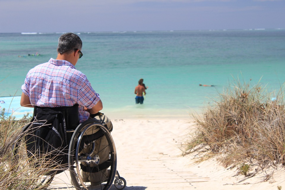 man in wheelchair on the beach