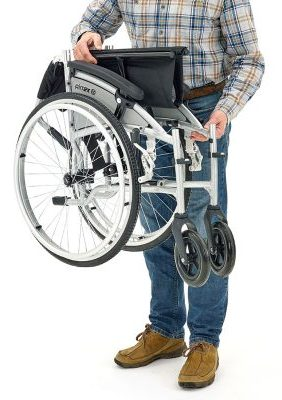 man carrying a folding wheelchair