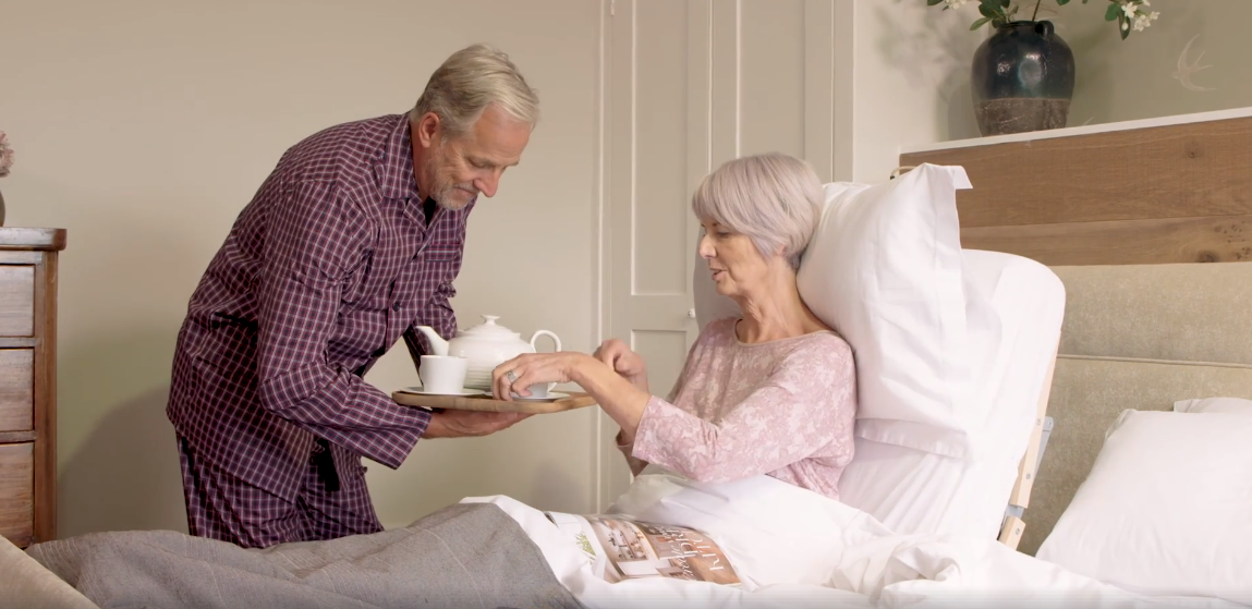 man serving a woman in adjustable bed