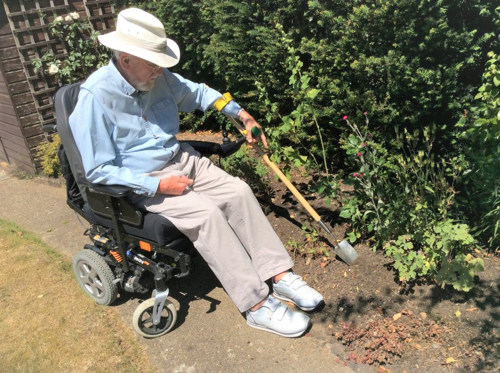 man using reach garden tool in powerchair
