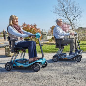 Couple riding together on their electric folding mobility scooters