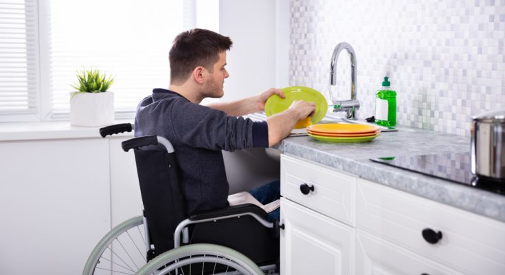 Man in wheelchair washing up in kitchen