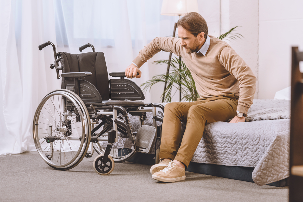 man moving from bed to wheelchair
