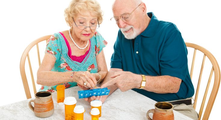 couple organising pills into a weekly reminder box