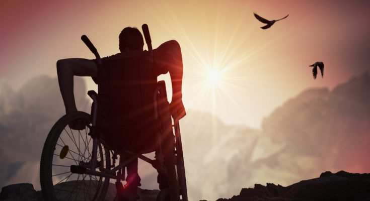 man in a wheelchair riding toward sun rise
