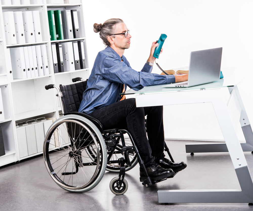 man in wheelchair sitting at a desk with poor posture