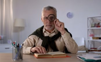 elderly man sat at table with book, looking through magnifying glass