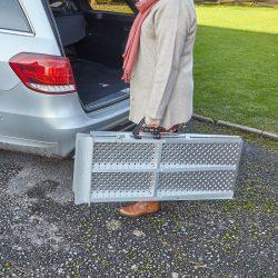 woman carrying Aerofold ramp to a car