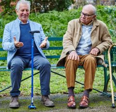 2 men sitting on a bench comparing walking sticks