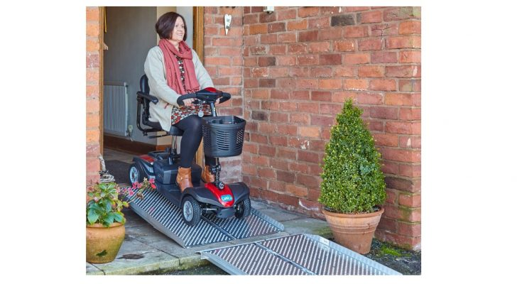 woman driving mobility scooter down an aerofold ramp