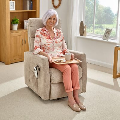 woman sitting on armchair with a handy tray on her lap