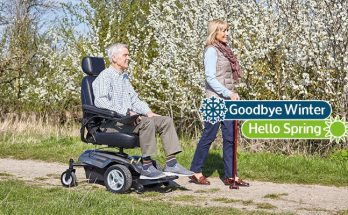 man in powerchair next to woman walking in a park