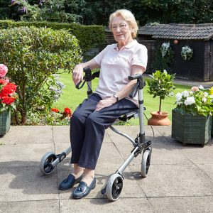 lady sitting on a 4 wheel zimmer frame